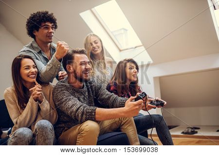 Group of friends playing video games at home.