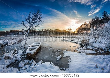 Frozen Boat On The Lake In Winter At Sunrise
