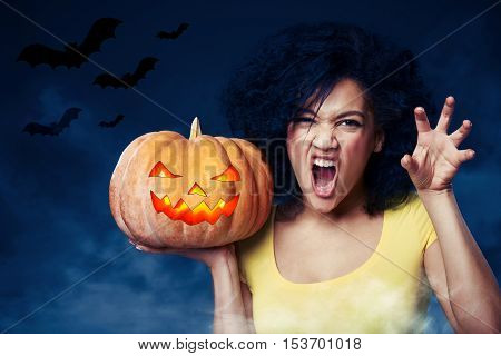 Young mixed race african american - caucasian woman holding Halloween pumpkin growling at you and gesturing a claw shape with her hands, over gray background with bats and smoke. Toned image