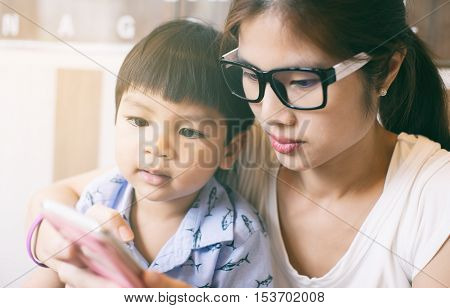 Mother teaching her child to use the smart phone.
