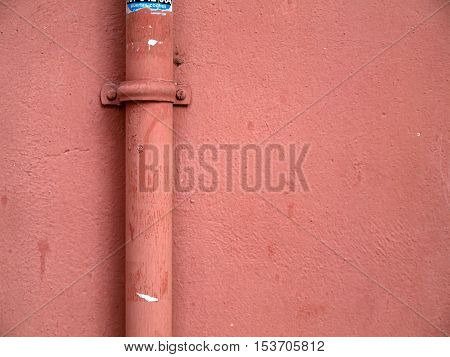 Detail of a pink wall with an old pipeline