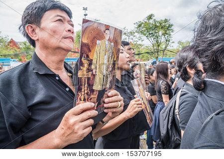 Bangkok Thailand - October 22 2016 : Thai people singing the anthem and hold the portrait of His Majesty King Bhumibol at Sanam Luang in front of the Royal Palace to pay respect for the king in Bangkok Thailand.