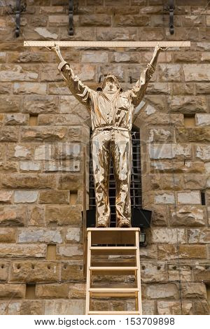 FLORENCE, ITALY - SEPTEMBER 2016 : Shiny bronze sculpture statue of The Man Who Measures the Clouds, man standing atop ladder with ruler in Florence, Italy on September 21, 2016. By Jan Fabre