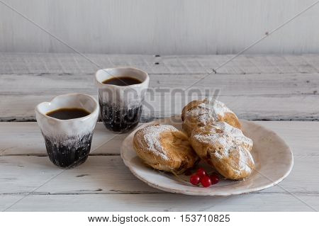 eclairs on a white background eclairs on a ceramic plate coffee and dessert eclairs and coffee