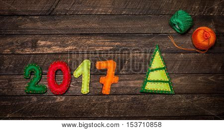 2017 Christmas tree made of felt. Childish New year background with christmas toy from felt on dark rustic wooden background. Holiday card - 2017 happy new year!