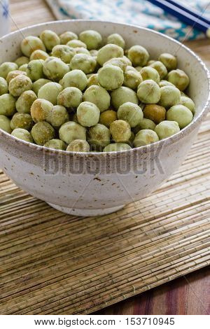 Wasabi peas a crunchy snack made with roasted green peas coated with wasabi seasoning in a Japanese ceramic bowl