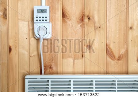 Working white electric convector heater plugged to timer power socket operated in smart house system against wooden wall inside room front view closeup