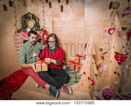 Happy family Holding Presents in Gift Shop - Beautiful smiling woman holding a pile of wrapped Christmas gifts