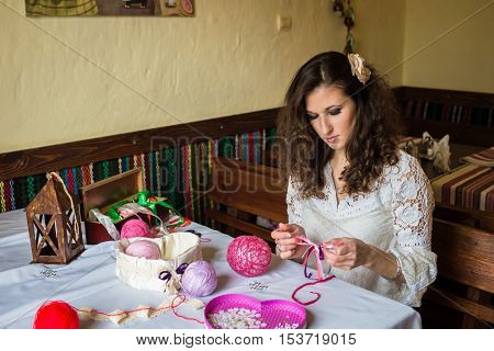 Girl makes balloon decoration with colored threads and ribbons