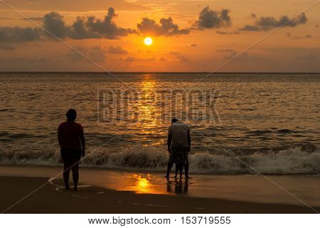 A family of three spend quality time at sunset at the beach