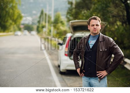 Hitchhiking - Need a drive. Young man on the road with his hand raised in front of car.
