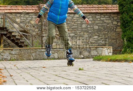 A young cute boy in a blue shirt with roller blades learning to skate on the road. Kids and sport. Hobby.