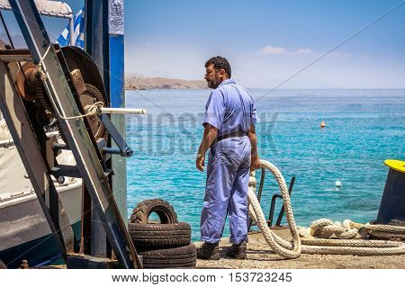 LOUTRO, CRETE, GREECE - JULY 2016: Man with rope at port of Loutro town on Crete island, Greece.