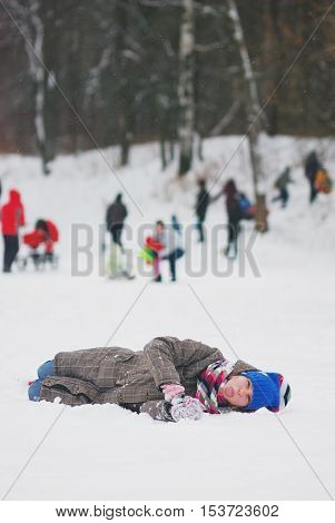 cute naughty girl lies on the snow and shows language in winter in a crowded Park
