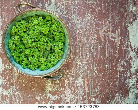 Clay bowl full of curly parsley on a wooden table