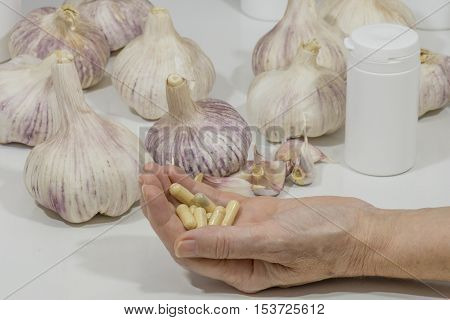 a hand showing capsules of garlic, garlic on the table