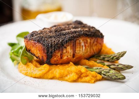 Salmon steak with asparagus and sweet potato mash served on white plate