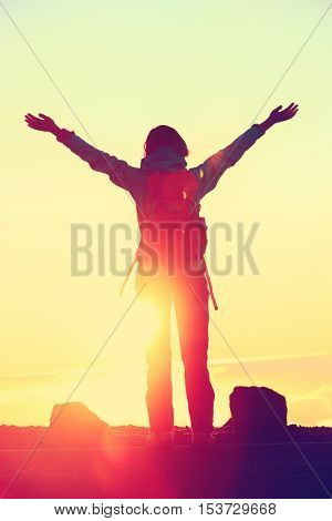Happy hiker freedom having reached summit goal with success at sunset. Silhouette of woman with backpack celebrating winning standing at mountain top with arms up in celebration during hiking travel.