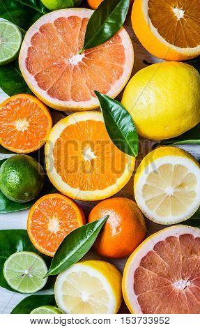 Citrus background. Assorted fresh citrus fruits with leaves. Lemon, orange lime, grapefruit mandarin. Harvest concept. Top view. White wooden background.