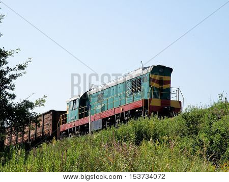 Shunting diesel locomotive with a composition rides on high embankments.