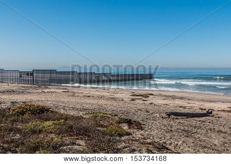 Border Field State Park beach with the international border wall separating San Diego, California and Tijuana, Mexico in the distance.