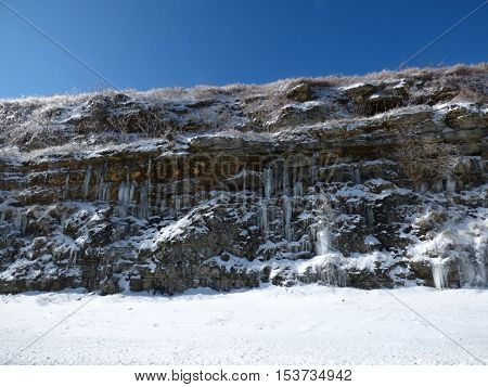 A road side hill that was cut down leaving underground springs leaking out of the hill side and freezing.