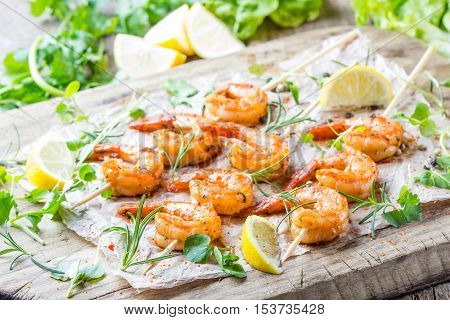 Seafood. Shelfish. Grilled fried Shrimps Prawns on wooden skewers with spices and fresh herbs on wooden rustic cutting table on wooden background. Srimps prawns brochette kebab. Barbecue srimp