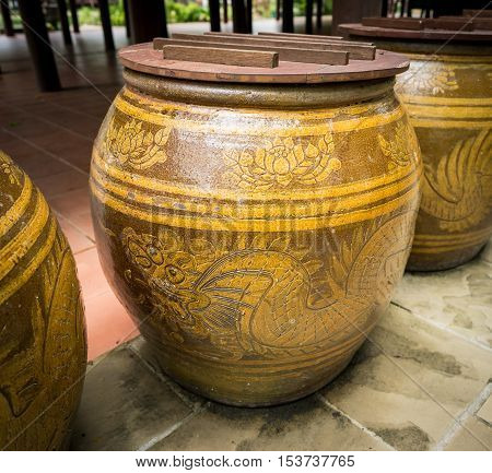 a big earthen jar made from clay with dragon pattern on side