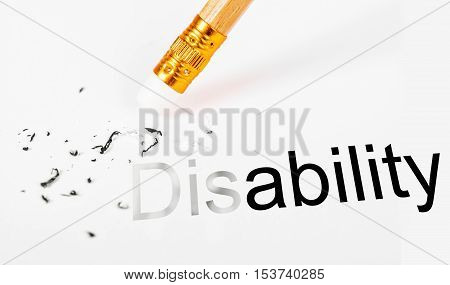Changing the word disability to ability with a pencil eraser on white paper.