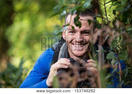 Portrait of smiling male hiker binoculars in forest