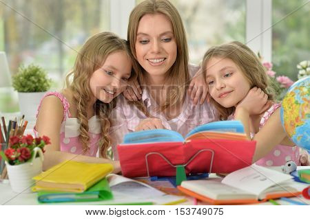Mother helping her daughters with homework at home