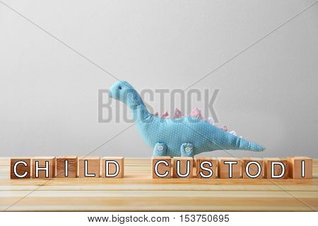 Word child custody made of wooden cubes and toy dinosaur on wall background
