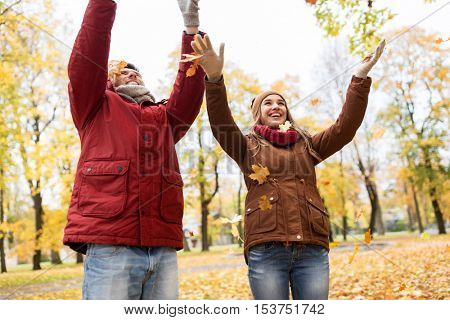 love, relationships, season and people concept - happy young couple throwing autumn leaves up in park