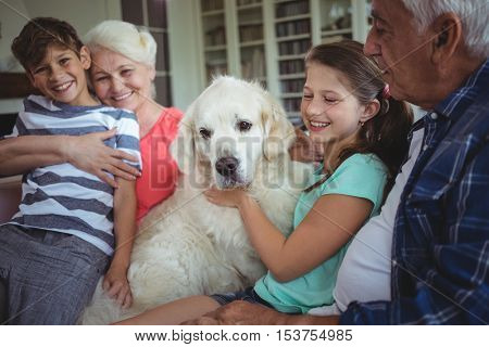 Happy grandparents and grandchildren sitting with pet dog at home
