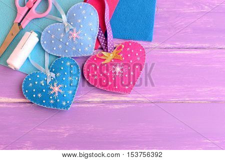Felt hearts crafts decorated with beads and snowflakes, scissors, thread, needles, felt sheets on lilac wooden background with blank copy space for text. Valentine's day winter wedding, Christmas diy