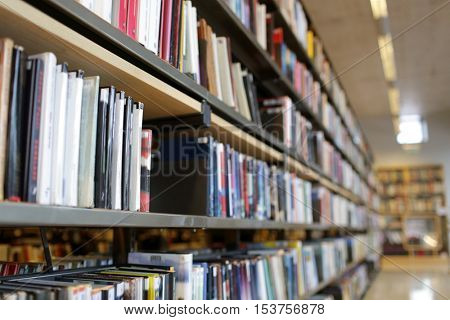 education, school, literature and knowledge concept - bookshelves with books at public library