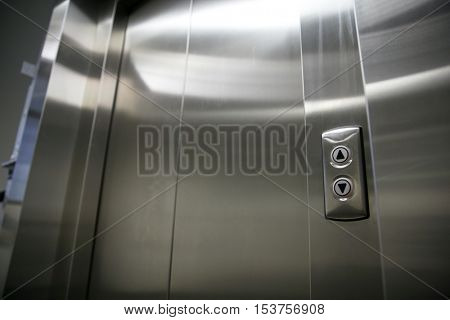 facility, transportation and equipment concept - modern elevator or lift closed metal doors and buttons