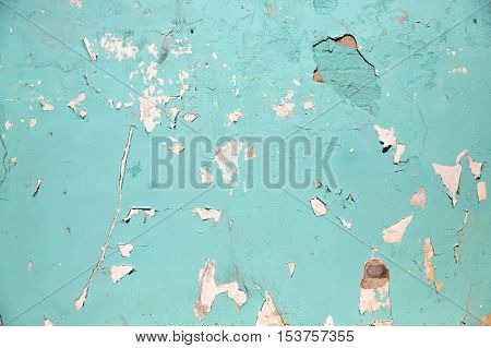 background and texture concept - blue or turquoise wall with peeling paint surface