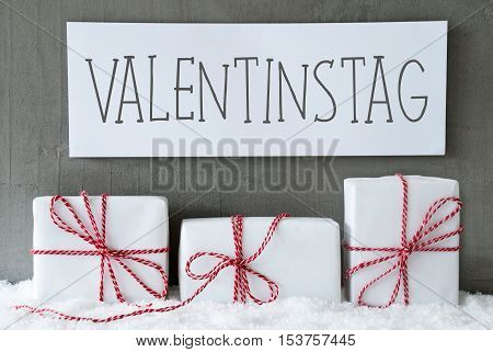 Label With German Text Valentinstag Means Valentines Day. Three Christmas Gifts Or Presents On Snow. Cement Wall As Background. Modern And Urban Style. Card For Birthday Or Seasons Greetings.