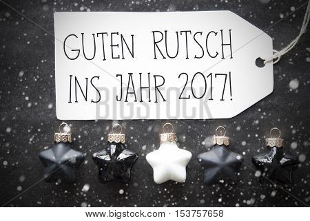 Label With German Text Guten Rutsch Ins Jahr 2017 Means Happy New Year 2017. Black And White Christmas Tree Balls On Black Paper Background With Snowflakes. Christmas Decoration With Flat Lay View