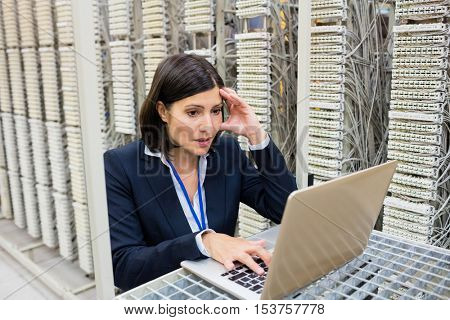 Tensed technician using laptop in server room