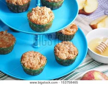Apple crumb spiced muffins with streusel topping on blue cake stand