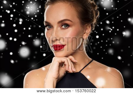 people, christmas, holidays, luxury and fashion concept - close up of beautiful woman with red lips over black background and snow