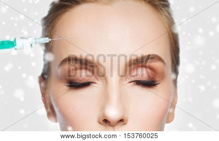 people, cosmetology, plastic surgery, anti-aging and beauty concept - close up of beautiful young woman face and syringe making lifting injection to forehead over gray background and snow