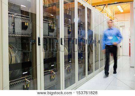 Technician walking in corridor of server room
