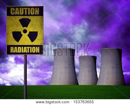 Nuclear power plant with radioactivity warning symbol in dramatic cloudy sky.
