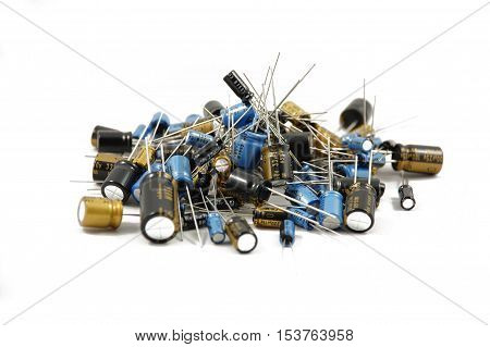 Many different  capacitors piled together on white background