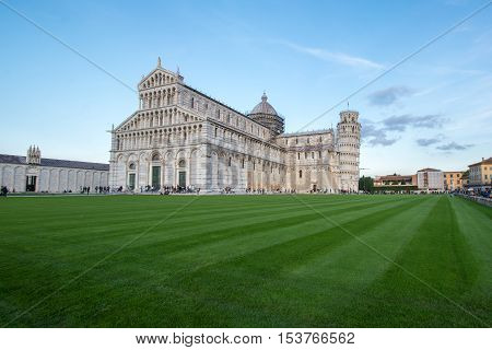 Pisa, Italy - October 22 2016: Tourists visiting the Leaning Tower of Pisa and Pisa Cathedral in Italy. The Tower of Pisa is one of Italy's most iconic tourist attractions and is famous worldwide for its unintended tilt.