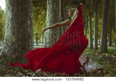 concept autumn blond woman with huge metal helmet and red cape, goddess of forests, fantasy