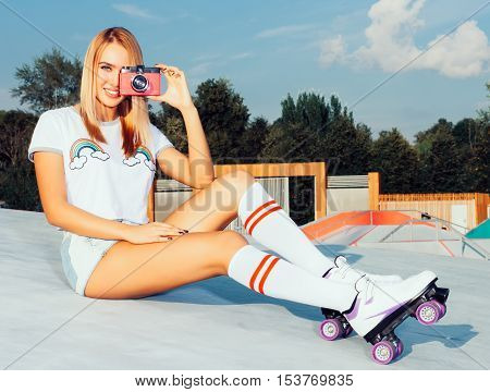 Beautiful blonde girl in denim shorts and white T-shirt, knee socks sitting on vintage roller skates in the skate park and taking photos pink vintage camera, warm summer sunny day. Rollers quads derby.